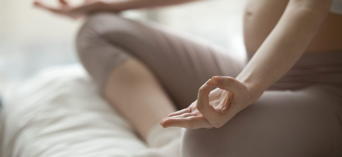 Close-up view of young pregnant woman doing morning yoga exercise after waking up at home. Yogi female model sitting cross-legged on the bed and meditating